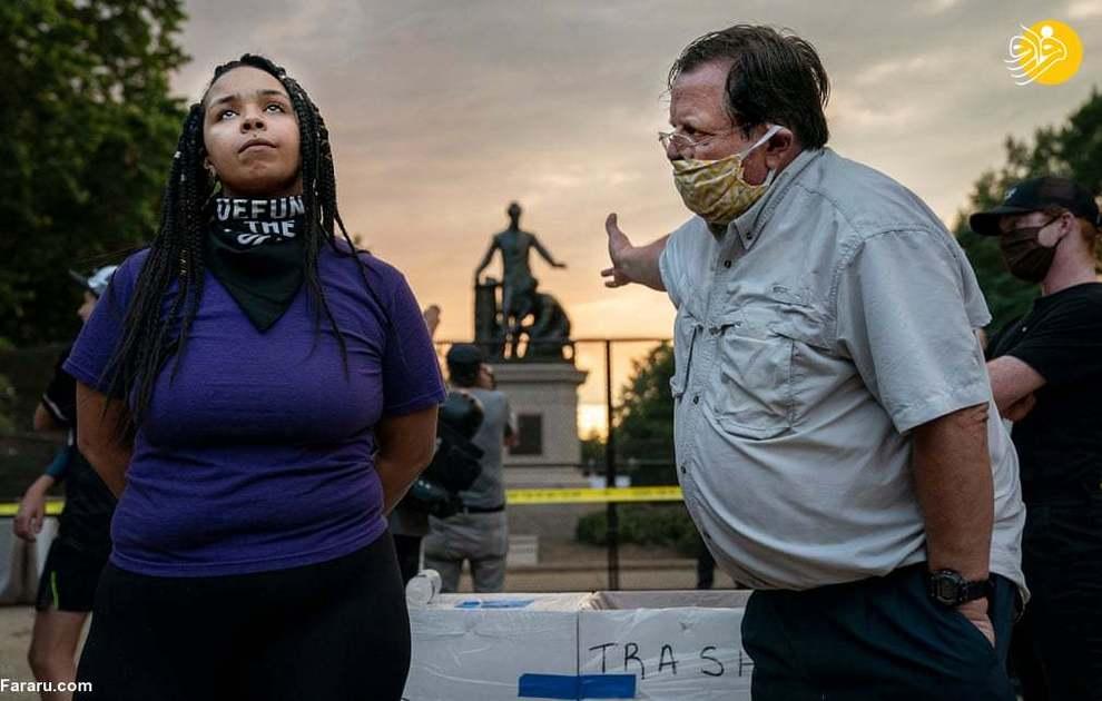 یک مرد سفیدپوست با زنی سیاهپوست بر سر معنای مجسمه رهایی در واشنگتن جروبحث میکنند. مجسمه رهایی تندیسی از آبراهام لینکن، رئیسجمهوری اسبق آمریکاست که اعلامیه لغو بردهداری را در یک دست دارد و دست دیگرش بر سر یک سیاهپوست به نشانه حفاظت قرار دارد. (عکاس: اویلین هاکشتین)